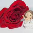 Cupid angel on the red rose — Stock Photo