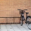 Black bike against a brick wall — Stock Photo