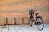 Black bike against a brick wall — Stock Photo