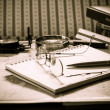Stock Photo: Vintage still life with old spectacles on book near desk lamp