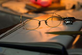 Vintage still life with old spectacles on book near desk lamp — Stock Photo