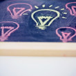 Stock Photo: Funny lightbulb on blackboard, concept of uniqueness