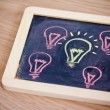 Funny lightbulb on blackboard, concept of uniqueness — Stockfoto