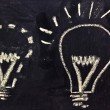 Building a concept, funny lightbulb on blackboard — Stock Photo