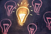 Funny lightbulb on blackboard, concept of uniqueness — Stock Photo