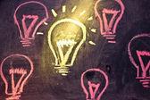 Funny lightbulb on blackboard, concept of uniqueness — Stock Photo