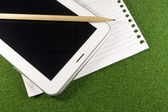 Tablet and line blank papers on nature green grass — Φωτογραφία Αρχείου