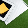 Digital Tablet with note pad and line papers on green grass — Stock Photo #35418363