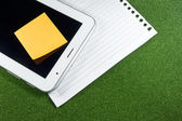 Digital Tablet with note pad and line papers on green grass — Stock Photo