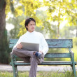 A young handsome man using laptop sitting on a bench looking in — Stock Photo #44437779