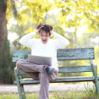 A young handsome man asian using laptop sitting on a bench in a — Stock Photo #44437861