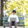 A young handsome man using laptop sitting on a bench in a park. — Stock Photo #44438097