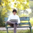 A young handsome man using laptop sitting on a bench in a park. — Stock Photo #44438149