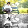 A young handsome man using laptop sitting on a bench in a park. — Stock Photo #44438253