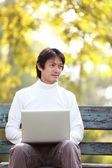 Młody, przystojny mężczyzna, za pomocą laptopa siedząc na ławce patrząc — Zdjęcie stockowe