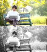 A young handsome man using laptop sitting on a bench in a park. — Стоковое фото