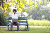 Młody przystojny mężczyzna za pomocą laptopa siedząc na ławce w azji — Zdjęcie stockowe