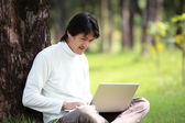 Young man using his laptop on the grass — Stock Photo
