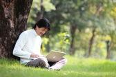 Młody człowiek za pomocą jego laptop na trawie — Zdjęcie stockowe