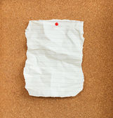 Wrinkled paper with red pin on cork board — Stock Photo