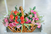 Artificial roses in the basket — Stock Photo