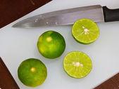 Limety a nůž. na dřevěné — Stock fotografie