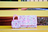 Luxury women bag on table in garden — Stockfoto