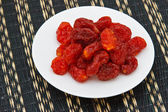 Healthy red fruit on white plate — Stock Photo