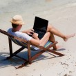 Man sitting on a deck chair with a laptop at the beach — Stock Photo