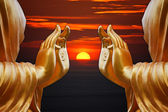 Hand Buddha statue with sunset sky background — Stock Photo