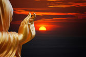 Hand Buddha statue with sunset sky background — Photo