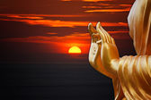 Hand Buddha statue with sunset sky background — Stok fotoğraf