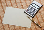 Calculator with notebook & pen on bamboo wooden background — Stock Photo