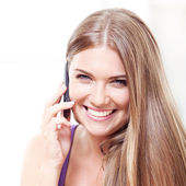 Happy woman at home sitting using mobile phone — Stock Photo