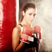 Female athlete with a punching bag — Stock Photo