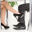 The Office Affair. Woman's foot looking for man's foot under a business table. — Stock Photo
