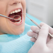 Little patient at dentist office. Little boy sitting at the chair at the dental office while doctor examining teeth — Stock Photo