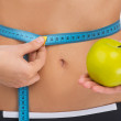 Healthy lifestyle concept. Close-up of woman torso holding an apple and measuring tape — Stock Photo