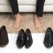 Which pair? Men choose which pair of shoes to wear — Stock Photo