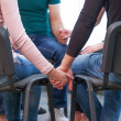 Group of people sitting in the cicrle and holding hands. — Stock Photo