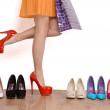 My favourite shoes. Close-up of female legs wearing red shoes while other shoes standing in the row — Stock Photo