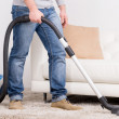 Vacuum Cleaner. A man does house work with a vacuum cleaner — Stock Photo