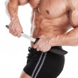 Stock Photo: Bodybuilder with knife. Muscular man pulls the knife out of its scabbard