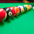 Stock Photo: Billiards. Close-up of billiard balls and cues on green table