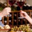 Cheers! Close up of people holding wine glasses at the restaurant — Stock Photo