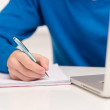 Student  writing. detail of a hand of man with blue shirt writing on a notebook with a pen — Stockfoto