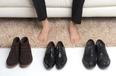 Which pair? Men choose which pair of shoes to wear — Стоковое фото
