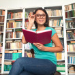 Stock Photo: Cheerful young woman holding book