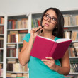 Thoughtful student. Beautiful young woman holding books and look — Stock Photo