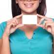 Woman with business card. Close-up of cheerful young woman holding business card while standing isolated on white — Stock Photo